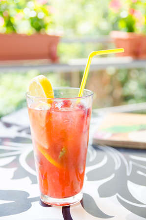 Strawberry and lemon cocktail with a yellow straw and a slice of lemon on a restaurant table
