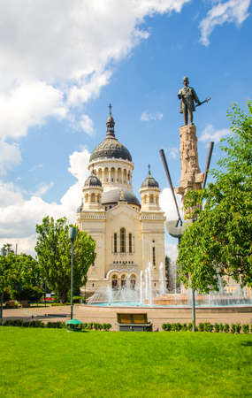 national hero: Cluj Napoca Orthodox Cathedral church with the statue of national hero Avram Iancu and fountain in the Square with the same name with fresh green grass and trees and a blue cloudy sky