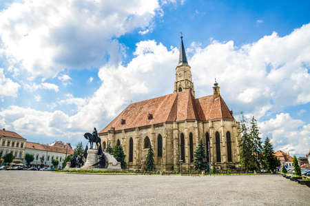 Cluj Napoca Unirii Square with the medieval gothic St Michael Church and the statue of Matei Corvin or Matias Rex on a sunny summer day with a beautiful sky in Transylvania region of Romania Stock Photo
