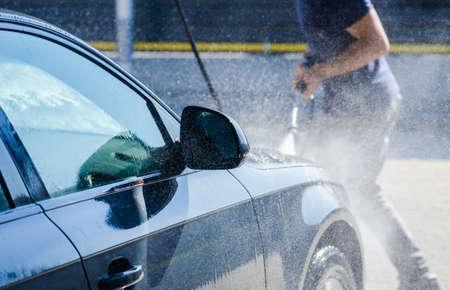 autolavado: Hombre que lava su coche y pulverizaci�n de agua por todas partes con un aspecto din�mico que sugiere los servicios de lavado de coches en una prima de Autovehicle Foto de archivo
