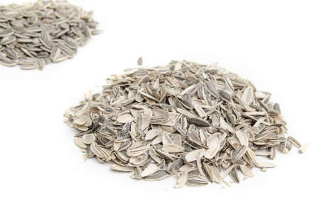 husks: Pile of husks in focus and a pile of sunflowers seeds out of focus on a white background
