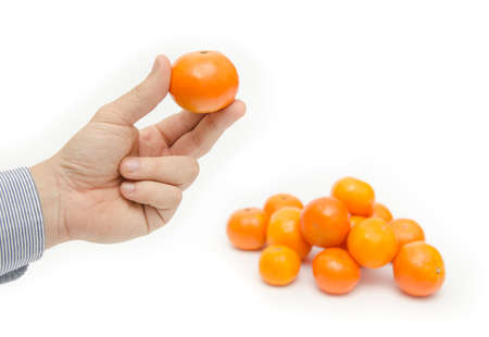 three fingers: Fresh orange fruit being held with three fingers by a business hand with a pile next to it on a white background suggesting vitamin filled exotic fruits Stock Photo