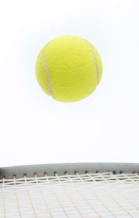 Raquet: Tennis ball jumping and levitating over a raquet suggesting the a stop motion on a game point