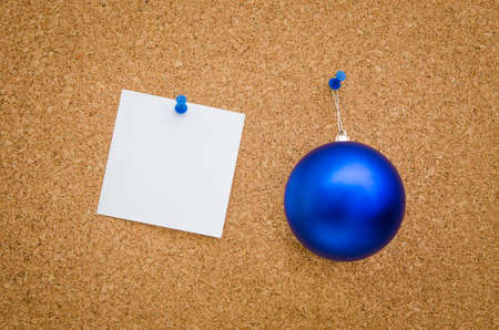 suggesting: Blue christmas globe and white paper with text space pinned to a board suggesting a business office holiday christmas greeting card
