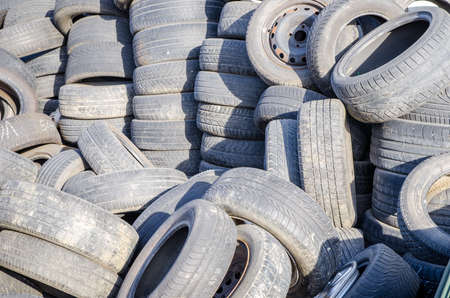 suggesting: Pile of used old tires on a sunny day suggesting automotive trash