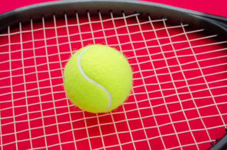 raquet: Tennis ball on a raquet with a red alerted serious background suggesting an important match set game or point in this great elegant sport