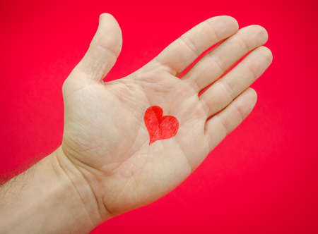 Love in a mans hands with lots of feelings and emotions from a relationship suggested by a heart drawn on a palm over a red background