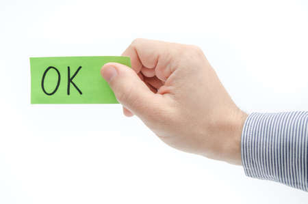 confirms: OK approval concept suggested by a green ticket in a business mans hand on a white background
