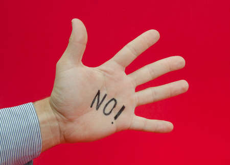 suggested: Talk to the hand or saying no to something suggested by a business mans hand with no writen on it on a red alerted background Stock Photo