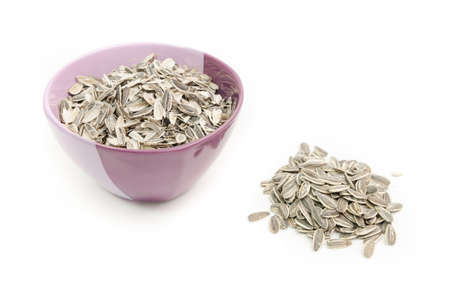 Sunflower seeds and husks in a bowl on a white isolated background with the peel in th bowl