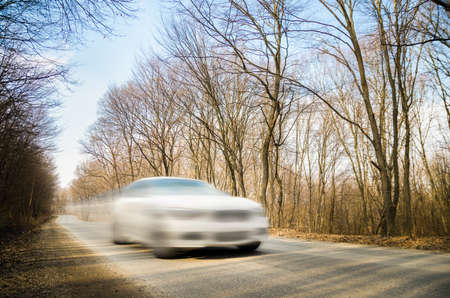 speeding: Speeding car with a motion look on a road through a leafless forest on a sunny autumn day. Soft filters applied