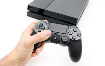 CLUJ-NAPOCA, ROMANIA - 25 FEBRUARY: Illustrative editorial image of Sony Playstation 4 console with Dualshock 4 controller in a mans hand on a white isolated background suggesting he is playing games on the latest gaming console with a high tech modern d