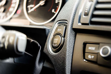 keyless: Auto start and stop button on a modern premium car interior suggesting fuel economy, modern technology and eco friendlyness on a bright sunny day with some light filters applied
