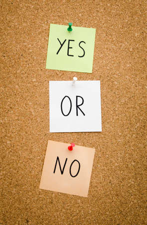 deny: YES OR NO written on red white and green post notes pinned to a board suggesting options to accept or deny in a bussines look in portrait mode