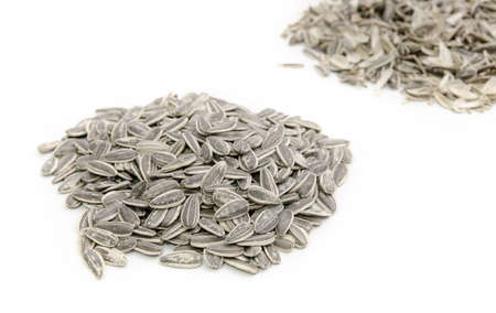Pile of sunflower seeds in focus and a pile of husks out of focus on a white background Stock Photo