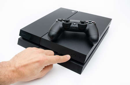 playstation: CLUJ-NAPOCA, ROMANIA - 25 FEBRUARY: Illustrative editorial image of Sony Playstation 4 console with Dualshock 4 controller  and a hand showing the PS$ logo