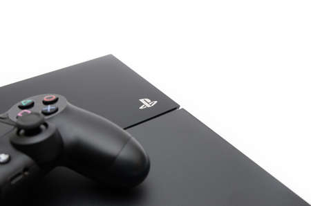 CLUJ-NAPOCA, ROMANIA - 24 FEBRUARY: Playstation 4 with the PS logo in focus and part of a dualshock 4 controller out of focus un a white isolated background suggesting modern game console branding