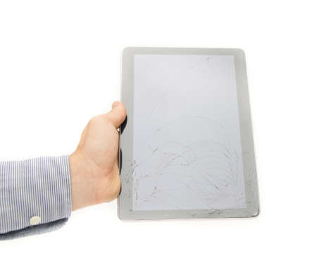 hand care: Cracked tablet touch screen display on a white background suggesting the need tu insure and protect your electronic device from dangers like breaking it because they are expensive to fix and repair and the warranty is limited coverege Stock Photo