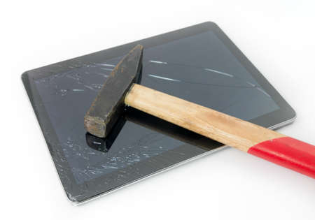 Hammer on a tablet with a cracked broken touchscreen glass suggesting the need for repair and service under warranty Stock Photo