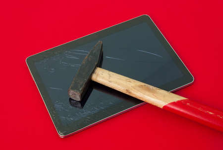 replace: Hammer on a broken touch screen tablet on a red alerted important dangerous serious background suggesting not an accident and glass replace Stock Photo