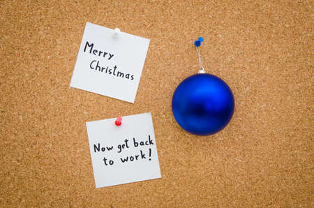 overworking: Merry Christmas but now get back to work written on notes next to a blue Christmas globe suggesting the boss is overworking the employee or a worcahoolic and stress for a funny greeting card