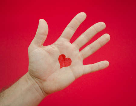 suggested: Emotions and feelings from loving somebody suggested by a mans open palm with a heart over a red seroius background