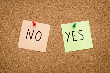 YES NO written on red white and green post notes pinned to a board suggesting options to accept or deny in a bussines look in landscape mode