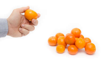 Hand holding a ripe orange with a pile next to it on a white isolated background suggesting fresh raw seasonal fruits with vitamins in a businedd work look
