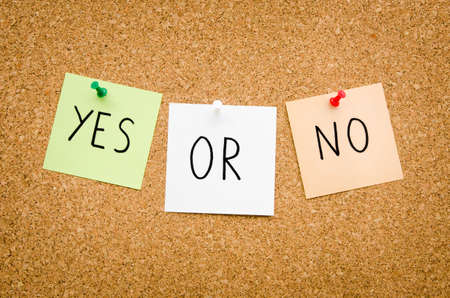 landscape mode: YES OR NO written on red white and green post notes pinned to a board suggesting options to accept or deny in a bussines look in landscape mode Stock Photo