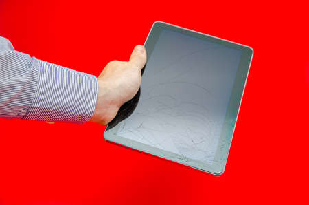 portable failure: Cracked touch screen display glass in a business mans hand on a red alerted background suggesting fragile electronics and fix and repair on expensive technology with an alerted look