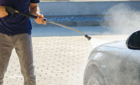 car lots: Man washing his car with a pressure cleaner with a blue look and lots of vapor