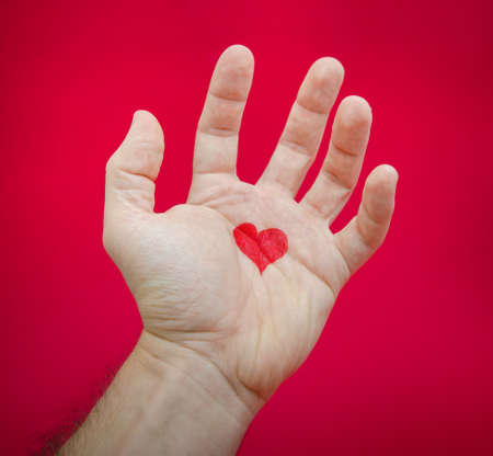 love hurts: Love hurts and creates pain after a relationship is over suggested by a heart on a hand suggesting frustration and pain on a red alerted seriuos background