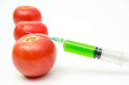 Toxic syringe on some fresh tomatoes indicating dna modification Stock Photo