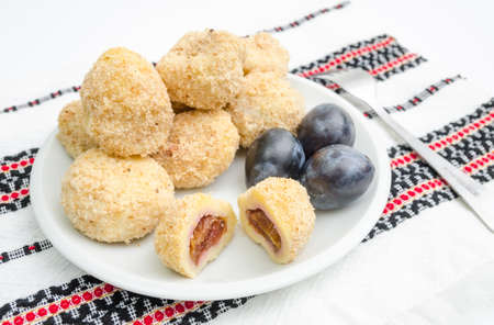 Traditional plum dumplings with prunes on a traditional romanian table cloth