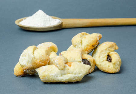 Traditional crescent rolls with plum jam and a wood spoon with flour on a gray background Stock Photo