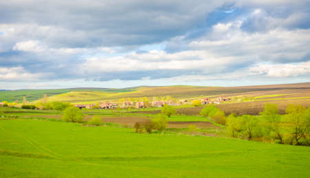 rural countryside: Rural countryside view with a village and farmland fields on a sunny spring day with a blue cloudy sky
