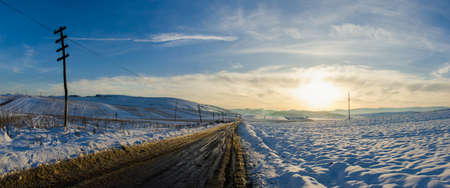 telegraph hill: Rural unpaved road waving over the hills and mountains on a snowy winter day at a bright melancolic sunset