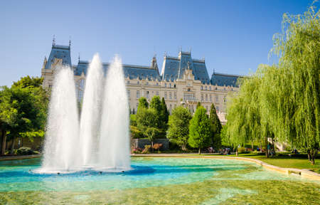 restauration: IASI, ROMANIA - 10 AUGUST 2014: Iasi Cultural Palace with a beautiful green park and people on a sunny summer day Editorial