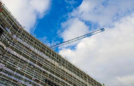 Construction site with a tall glass building and a crane on a sunny summer day with a blue cloudy sky Stock Photo