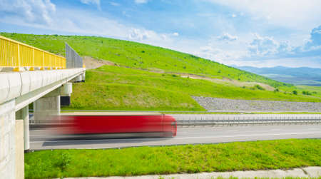 Speeding fast red truck on a highway over the green hills on a sunny summer day with a bright blue cloudy sky and a bridge with a yellow railing suggesting quick and serious cargo transport delivery and shipping services with a motion look
