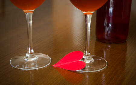 dimm: Love and romance suggested by a red heart two wine glasses and a bottle of rose wine on the background in a dimm romantic light Stock Photo