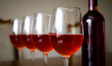A glass of rose red wine with three others on the background and a bottle with a soft slow melancolic mood and feel