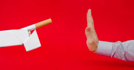 Say no to smoking suggested by a business man refusing a pack of cigarettes on a red serious alerted important background with a dangerous look Stock Photo