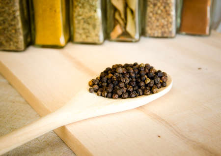 Pepper in a wood spoon on a wood board with herbs on the background Stock Photo