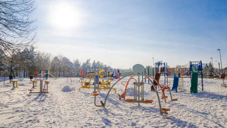 Childrens playground on a sunny winter day with white snow and a cold feel Stock Photo