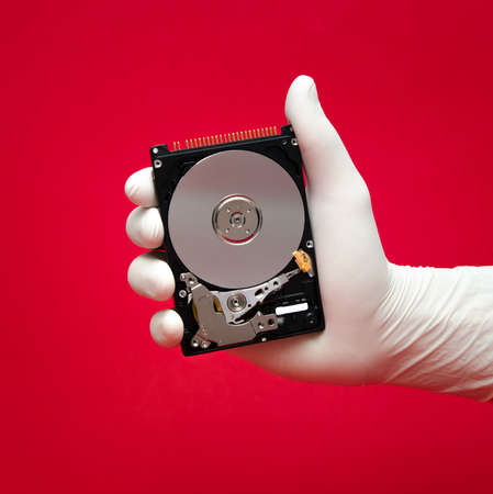 portable hard disk: A hard disk being held by a scientist or repairmans hand on a red with valuable files awaiting to be recovered