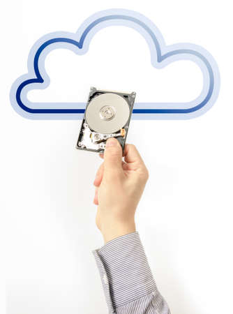 Cloud storage and computing suggested by a business mans hand holding a hard disk drive