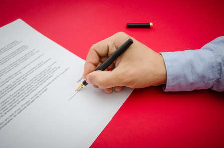 Sign here suggested by signing the document or contract by a business man hand on a red alerted background