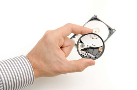 recover: A tech guy inspecting a hard disk through a magnifying glass looking for broken pieces in order to recover files and data