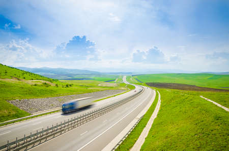 Speeding shipping transport truck on a highway waving over the hills with a fast quick motion look on a sunny day with green grass and a blue cloudy sky Stock Photo